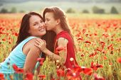 foto of preteen  - Mother and her 7 years old preteen child playing in spring poppy field in soft sunlight - JPG