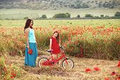 picture of preteen  - Preteen girl on bicycle with mother in spring field - JPG
