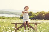 image of preteens  - 8 years old preteen girl sitting on rustic bench in flower field - JPG