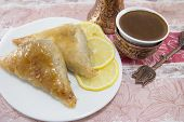 stock photo of baklava  - Turkish baklava and coffee on a plate with sliced lemons - JPG
