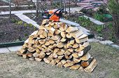 stock photo of chainsaw  - Stabel of chopped birch wood and a chainsaw in the yard - JPG