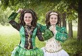 stock photo of wig  - Two young beautiful girl in irish dance dress and wig posing outdoor - JPG