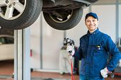 picture of auto repair shop  - Mechanician changing car wheel in auto repair shop - JPG