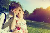 pic of fiance  - Young romantic couple kissing with love in sunny summer park - JPG
