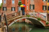stock photo of rainy day  - Man with colorful umbrella on picturesque bridge over Venetian canals on a rainy day - JPG