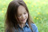 stock photo of shy girl  - Shy girl with long hair among dandelion field - JPG
