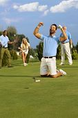 pic of fist  - Young male golfer kneeling happy at hole after successful putt - JPG