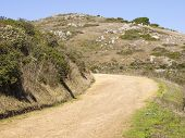 foto of bend  - A dirt road and path bends and disappears around a corner on dry hills of the Marin Headlands in Northern California - JPG