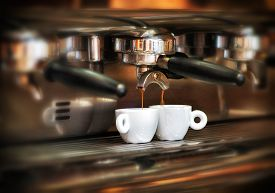 stock photo of brew  - Italian espresso machine on a counter in a restaurant dispensing freshly brewed coffee into two small cups to be served to customers  - JPG