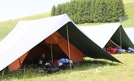 image of boy scout  - big tent of boy scout camp with backpacks and sleeping bags spread out - JPG