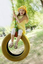 picture of tire swing  - Happy girl in yellow dress on tire swing - JPG