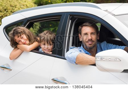 Children sitting in the car looking out windows. Cute children in car going camping with father. Sma