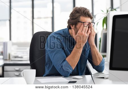 Portrait of an upset businessman at desk in office. Businessman being depressed by working in office