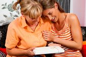 Two women �¢�?�? mother and daughter �¢�?�? sitting on a couch; the daughter has given her m