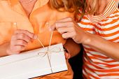 Two women �¢�?�? mother and daughter �¢�?�? sitting on a couch; the daughter has given her mother a gift
