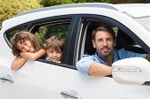Children sitting in the car looking out windows. Cute children in car going camping with father. Sma poster
