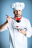 Portrait of a man cook holding a plate and ladle. Shot in a studio over grey background.