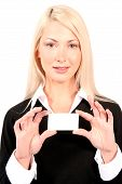 Beautiful Blonde Business Woman Holding Business Card In Front Of Her With Both Hands