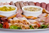 picture of cabana  - Close up of cold meat catering platter with cold cuts of meat including sliced chicken breast mortadella salami roast beef ham turkey cabana sausage and seeded wholegrain mustard and sweet mustard pickle - JPG
