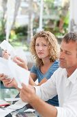 Desperate couple calculating their domestic bills at home poster