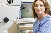 Portrait Of A Nurse Next To An Eye Exam Machine