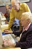 Senior man helping senior woman to use computer