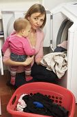 Woman Doing Laundry And Holding Baby Daughter