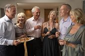 Man Serving Hors D'oeuvres To His Guests At A Dinner Party