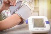 Womens hand with blood pressure monitor cuff. Checking blood pressure at home concept poster