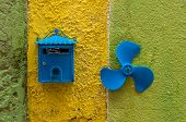 Blue Mailbox And Small Propeller On Colored Wall In Alley Of Italian Old Town poster
