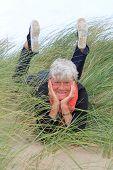 Lachende vrouw in haar jaren zeventig vaststelling van buiten in het gras.