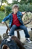 picture of young boy  - happy 7 yr old boy having fun sitting on old farm tractor plaid jacket and jeans - JPG