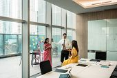 Three Indian employees talking during break in the meeting room of a modern business building poster