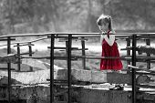 Black And White Picture Of Pretty Blond Child Girl In Red Dress Standing Alone On Old Bridge Leaning poster