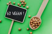 Gold Chickpeas In Wooden Spoon On Green Background And A Chalkboard With The Text Go Vegan, Tasty Ve poster