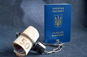 Ukrainian Biometric Passport And Handcuffs With Money On The Table poster