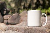 White Blank Coffee Mug Mock Up, Close-up Of Mug Outside In The Sunshine On Some Large Decorative Gar poster