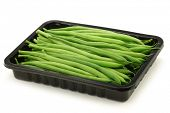 small and slender green beans (haricot vert) in a black plastic container on a white background