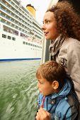 Mutter und Sohn sehen auf großen Kreuzer aus dem Schwimmen sie weg auf Schiff