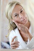 Attraktive Frau mittleren Alters, Billigbücher im Gesicht anwenden