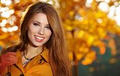 stock photo of red hair  - Beautiful elegant woman standing in a park in autumn - JPG