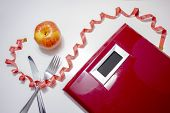 Losing Weight Concept. Weight Scale With A Fork, Knife, Red Measuring Tape And An Apple poster