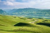 Landscape Of Alpine Meadows With Road And River Among Mountain Ranges,cattle Are Grazing In The Past poster