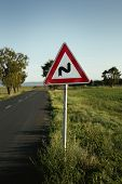 Photo Of Illuminated And Warning Road Sign - Double Curve Next To The Road On Meadow. Double Bend Wa poster