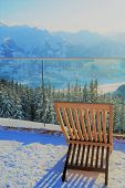 Lounging In The Alps. A Single Lounge Chair In The Snow To Enjoy The Spectacular Mountaintop View Fr poster
