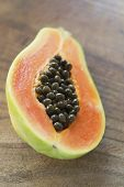 Halved Papaya On Wooden Surface Showing Seeds