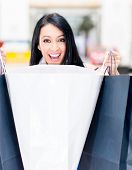 Surprised female shopper opening shopping bags and smiling