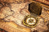 Vintage pirate retro compass on ancient world map. The map used for background is in Public domain.
