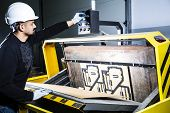 Worker In A Hard Hat Turning On A Punching Machine. Cardboard Boxes Factory. Paper Die Cutting Machi poster