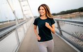 Portrait Of Fit And Sporty Young Woman Jogging Outdoor poster